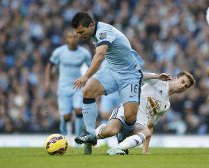 Manchester City's Sergio Aguero is challenged by Swansea City's Tommy Carroll during their English Premier League soccer match at the Etihad stadium in Manchester