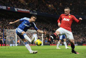 Wayne Rooney of Manchester United blocks a clearance by Gary Cahill of Chelsea